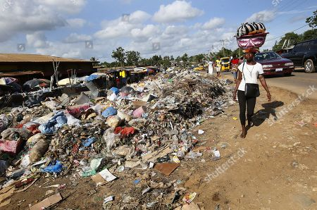 A Liberian woman carrying her belongings  wrapped in plastic bags walks past an illegal dump site filled with plastic waste adjacent a roadside in Monrovia, Liberia 29 May 2018. Plastic pollution has reached epidemic proportion. According to an Ellen MacArthur Foundation report there will be more plastic in the ocean than fish by 2050. Africa is one of the most affected continents due to its extensive coastline and underdeveloped waste systems allowing plastic waste to easily enter the ocean.  The rapid growth of plastic production in the three biggest areas the European Union, China and the US particularly in single-use plastics is recognised as one of the greatest risks facing the environment and mankind. Efforts at recycling and plastic waste education are on the rise on the African continent with many programs being initiated by youth groups who view the problem as the biggest environmental challenge facing the new generation.