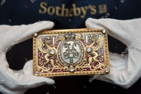 """A Sotheby's technician presents """"An Imperial Presentation Fabergé jewelled gold and enamel box"""", 1897, by Michael Perchin (Est. GBP150-200k) at a preview of the Russian Pictures and Russian Works of Art, Fabergé & Icons sale which will take place at Sotheby's, New Bond Street on 5 June."""