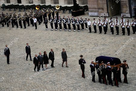 Stock Photo of The Children of late Serge Dassault, Chairman and CEO of Dassault Group, from left to right, Laurent Dassault, Olivier Dassault, Marie-Helene Habert-Dassault and Thierry Dassault, center, walk behind their father's coffin, followed by French Prime Minister Edouard Philippe, left, during the funeral ceremony at Hotel des Invalides in Paris, France, . French business executive Serge Dassault, a top aviation and arms industrialist, has died in his Paris office. He was 93
