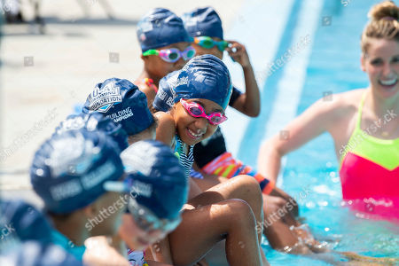 Stock Image of A class of children are taught to swim by USA Swimming Foundation ambassadors and Olympic gold medalists Missy Franklin and Cullen Jones along with Sports Illustrated Sports Kid of the Year, Reece Whitley as part of USA Swimming Foundation's Make a Splash initiative on in Washington, DC