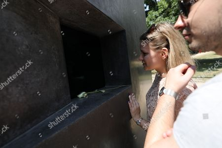 Stock Image of People watch a film of homosexual couples kissing, part of a memorial designed by Michael Elmgreen and Ingar Dragset opposite the Holocaust Memorial at the Tiergarten in Berlin, Germany, 01 June 2018. Through the small square window the spectator can see a film depicting a kiss serving as a memorial to the homosexual victims of National Socialism and as a lasting symbol against exclusion, intolerance and animosity towards gays and lesbians.