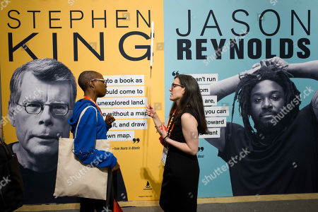 Women attending Book Expo stand in front of promotional posters for authors Stephen King and Jason Reynolds, in New York