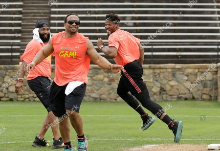 Cam Newton, Jamal Anderson. Carolina Panthers' Cam Newton, right, runs past former NFL player Jamal Anderson, center, during the NFL football star's charity kickball tournament in Charlotte, N.C