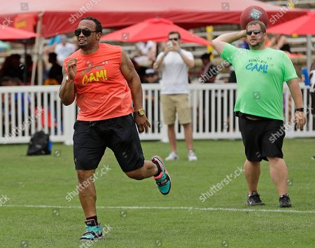 "Former Atlanta Falcons' Jamal Anderson, left, performs the ""dirty bird"" as he runs the bases during Carolina Panthers' Cam Newton's charity kickball tournament in Charlotte, N.C"