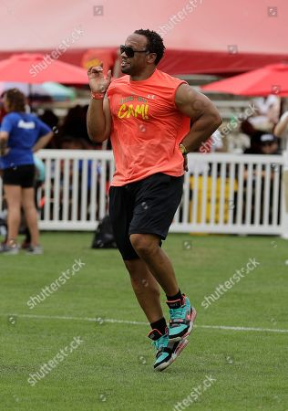 "Former Atlanta Falcons' Jamal Anderson performs the ""dirty bird"" as he rounds the bases during Carolina Panthers' Cam Newton's charity kickball tournament in Charlotte, N.C"
