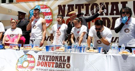 Competitors finish their last donut as time is called after eight minutes of donut eating at 2nd Annual National Donut Day World Donut Eating Championship in Hollywood, California, USA, 01 June 2018.  The competition is sponsored by the Salvation Army and is part of its fundraising challenge to benefit veterans. Matt Stonie (3rd L) won the competition by eating 48 donuts.