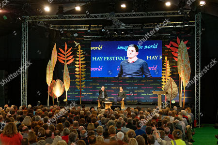 Former MP David Miliband (R) talks to James Naughtie (L) in the Tata Tent