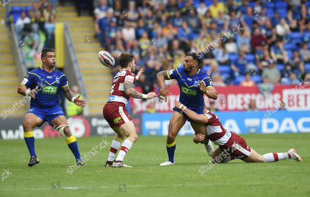 Ryan Atkins of Warrington Wolves passes the ball to Ben Murdoch-Masila as he is tackled by George Williams of Wigan Warriors