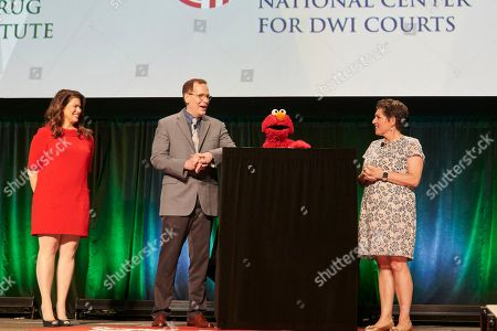 Stock Picture of Carson Fox, Jeanette Betancourt. Carson Fox, CEO of the National Association of Drug Court Professionals, and Jeanette Betancourt, Senior VP, Community and Family Engagement at Sesame Workshop, discuss their partnership to provide resources to children and families in need with special guest Elmo, while Melissa Fitzgerald, Director of NADCP's Advancing Justice Initiative looks, during the closing ceremonies of the National Association of Drug Court Professionals annual training conference, in Houston