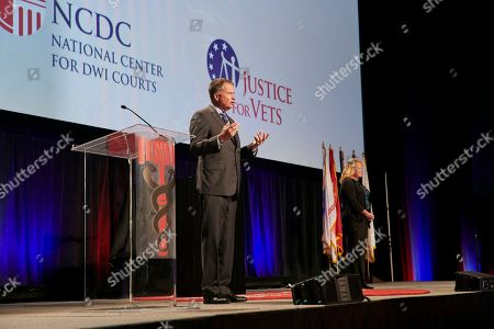 Stock Photo of Retired Navy Admiral James Winnefeld and his wife Mary, founders of S.A.F.E. Project U.S., address justice and treatment professionals during the closing ceremonies of the National Association of Drug Court Professionals annual training conference, in Houston