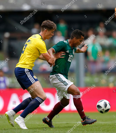 Giovani dos Santos, Jack Hendry. Scotland's Jack Hendry, left, pressures Mexico's Giovani dos Santos, during a friendly soccer match at Azteca Stadium in Mexico City