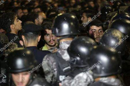 Stock Photo of Jordanian security forces block protesters trying to get to the Prime Ministry, during a demonstration against the newly proposed income tax reforms and hike in petrol tax, in Amman, Jordan, 03 June 2018. The newly announced income taxes law has been prepared and sent to the parliament, and the protesters demand its withdrawal. The spokesman for the Jordanian professional associations and President of Jordan Doctor's Association Dr Ali Al Abous announced on 02 June a call for mobilization gathering to take place 06 June, one week after the first one, as its demands remained to be met.