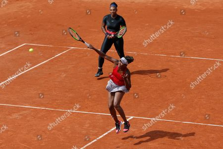 Serena Williams of the U.S., background, and her sister Venus Williams return the ball to Slovenia's Andreja Klepac and Spain's Maria Jose Martinez Sanchez during their double match of the French Open tennis tournament at the Roland Garros stadium, in Paris