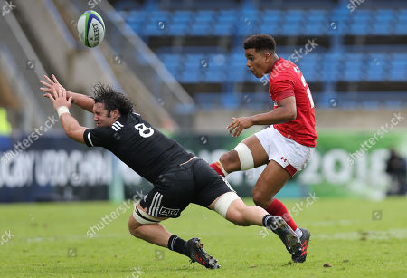 Ben Thomas of Wales kicks the ball past Devan Flanders of New Zealand