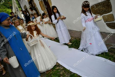 Young devotees take part during the Corpus Christi procession, in the small town of Bera de Bidasoa, northern Spain, . The day of Corpus Christi, dated on May 31, has ceased to be a public holiday in Spain. Then, people celebrated today this holy day, an ancient Catholic tradition for fervent believers