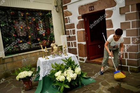 A woman sweeps the hall of her house beside to an altar before the Corpus Christi procession, in the small town of Bera de Bidasoa, northern Spain, . The day of Corpus Christi, dated on May 31, has ceased to be a public holiday in Spain. Then, people celebrated today this holy day, an ancient Catholic tradition for fervent believers