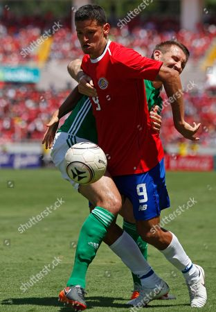 Costa Rica's Daniel Colindres, front, fights for the ball with Northern Ireland's Gareth McAuley during a friendly soccer match in San Jose, Costa Rica