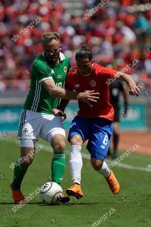 Costa Rica's Bryan Oviedo, right, and Northern Ireland's Aaron Hughes fight for the ball during a friendly soccer match in San Jose, Costa Rica