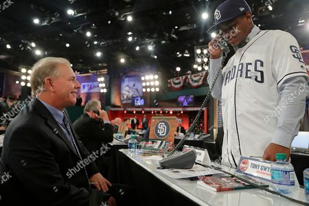 John Martin, left, watches as Xavier Edwards, a shortstop from North Broward Preparatory High School in Florida, talks on the phone with a member of the San Diego Padres after being selected No. 38 during the first round of the Major League Baseball draft, in Secaucus, N.J