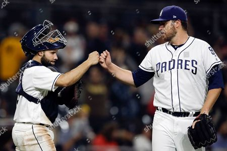 San Diego Padres catcher Raffy Lopez, left, and relief pitcher Phil Hughes, right, celebrate after defeating the Atlanta Braves in a baseball game, in San Diego. The Padres won 11-4