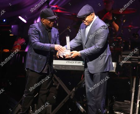 Sway Calloway, LL Cool J. Sway Calloway is seen presenting to actor and rapper LL Cool J at the 13th Annual Apollo Theater Spring Gala, in New York