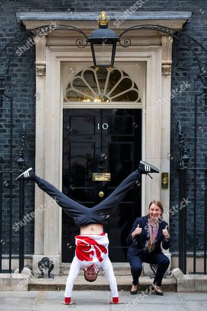 Gold medal winning gymnast Dominick Cunningham (L) performs a handstand with Sports Minister Tracey Crouch MP (R) outside 10 Downing Street.