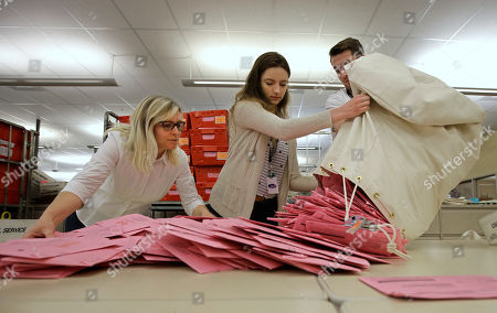 Election workers Heidi McGettigan, left, Margaret Wohlford, center, and David Jensen, unload a bag of ballots brought in a from a polling precinct to the Sacramento County Registrar of Voters office, in Sacramento, Calif