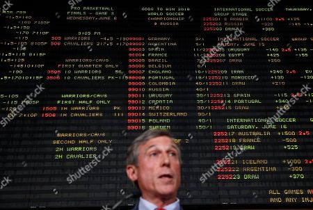Sports betting odds are displayed on a tote board behind Delaware Gov. John Carney, as he introduces sports gaming inside the Race and Sports Book at Dover Downs Hotel and Casino in Dover, Del. The market for legal sports gambling in the United States widened significantly on Tuesday with the expansion of single-game sports bets in Delaware, less than a month after the U.S. Supreme Court cleared the way for states to accept the bets