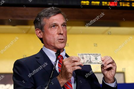 Delaware Gov. John Carney displays a ten dollar bill before using it to place a bet on a baseball game between the Chicago Cubs and the Philadelphia Phillies, inside the Race and Sports Book at Dover Downs Hotel and Casino in Dover, Del. The market for legal sports gambling in the United States widened significantly on Tuesday with the expansion of single-game sports bets in Delaware, less than a month after the U.S. Supreme Court cleared the way for states to accept the bets