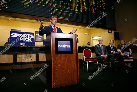 Delaware Gov. John Carney speaks in front of a tote board, as he introduces sports gaming inside the Race and Sports Book at Dover Downs Hotel and Casino in Dover, Del. The market for legal sports gambling in the United States widened significantly on Tuesday with the expansion of single-game sports bets in Delaware, less than a month after the U.S. Supreme Court cleared the way for states to accept the bets