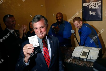 Delaware Gov. John Carney displays a receipt for a bet he placed on a baseball game between the Chicago Cubs and the Philadelphia Phillies, inside the Race and Sports Book at Dover Downs Hotel and Casino in Dover, Del. The market for legal sports gambling in the United States widened significantly on Tuesday with the expansion of single-game sports bets in Delaware, less than a month after the U.S. Supreme Court cleared the way for states to accept the bets
