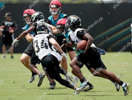 Charlie Miller, Jalen Myrick. Jacksonville Jaguars' Jalen Myrick, right, returns a kickoff as he picks up a block from teammate Charlie Miller (34) during an NFL football practice, in Jacksonville, Fla