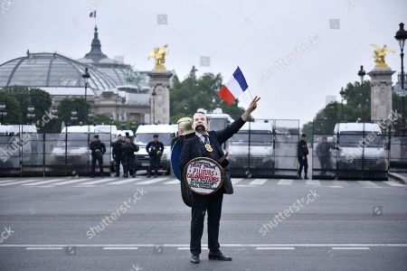 Stock Image of A demonstrator wears a mask of President Emmanuel Macron with a sign reading 'Looter - Colonizer' during a pro Palestinian protest against Israel Prime Minister Benyamin Netanyahu's visit near the Invalides in Paris, France, 05 June 2018. French President Emmanuel Macron and Israeli Prime Minister Benjamin Netanyahu had a meeting at the Elysee Palace.