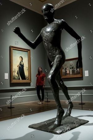 Stock Photo of (L) 'Queen Elizabeth II', 1955, by Pietro Annigoni and a sculpture 'The Running Man', 1978, by Dame Elisabeth Frink