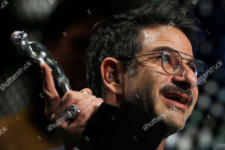 """Mexican actor Miguel Rodarte holds up his trophy after he was named best supporting male actor for his role in """"Tiempo compartido"""", at the Mexican Ariel Film Academy Awards ceremony at the Bellas Artes Palace in Mexico City, . The Ariel Awards recognize excellence in motion picture making, such as acting, directing and screen writing in Mexican cinema"""