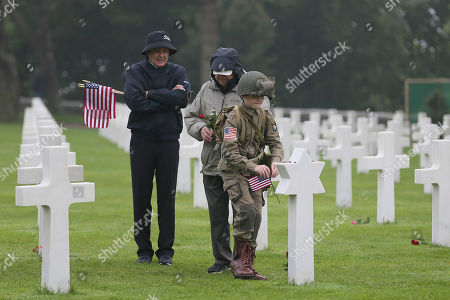 David Chamberlain, left, grandfather Charly Powers and his son Steve, from Atlanta, Georgia, pay their respect by putting down a US flag on the grave of US soldiers who died during the WWII war the Colleville American military cemetery, in Colleville sur Mer, western France, on the 74th anniversary of the D-Day landing