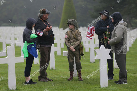 Stock Picture of David Chamberlain, second right and his family, from left to right, his wife June, his son Steve, center, and grandfather Charly Powers, from Atlanta, Georgia, visit the Colleville American military cemetery, in Colleville sur Mer, western France, on the 74th anniversary of the D-Day landing. U.S. and other allied troops have joined veterans of the D-Day invasion and families of fallen soldiers to mark 74 years since the massive military operation that change the course of World War II
