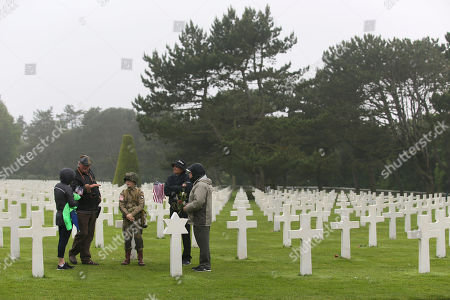 David Chamberlain, second right and his family, from left to right, his wife June, his son Steve, center, and grandfather Charly Powers, from Atlanta, Georgia, visit the Colleville American military cemetery, in Colleville sur Mer, western France, on the 74th anniversary of the D-Day landing