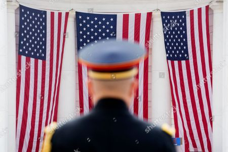 A member of a US military band is seen in front of US national flags during the Robert Francis Kennedy memorial service at Arlington National Cemetery Memorial Amphitheater, in Arlington, Virginia, USA, 06 June 2018. The event was held to honor the life and legacy of Robert F. Kennedy, who was assassinated in Los Angeles, dying in the early hours of 06 June 1968.