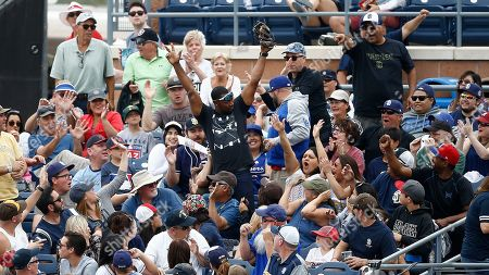 Stock Picture of A fan reacts after catching a foul ball during the third inning of a spring training baseball game between San Diego Padres and the Cleveland Indians, in Peoria, Ariz. A legend was made, when a foul ball hit by Atlanta Braves' Ender Inciarte landed in Gabby DiMarco's full cup of beer during the fifth inning of a baseball game against the San Diego Padres, in San Diego. DiMarco then stood up and chugged her entire drink
