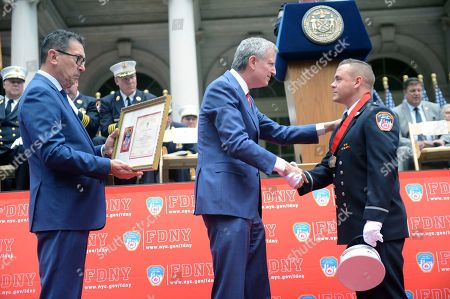 Mayor Bill de Blasio (center) and Fire Commissioner Daniel Nigro (left) present FDNY Lieutenant Joseph Costa (right) with the Dr. John F. Connell Medal at the annual FDNY Medal Day Ceremony at City Hall on where 67 FDNY Firefighters, Paramedics, EMTs, Fire Marshals and Officers are honored for their life-saving work. Costa was honored for rescuing a mother and her three children from a Queens fire