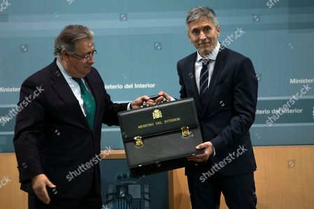 Fernando Grande-Marlaska, Juan Ignacio Zoido. New Interior Minister Fernando Grande-Marlaska, right, receives a briefcase from outgoing Minister Juan Ignacio Zoido during the handing over of the ministerial responsibilities at the Interior Ministry in Madrid, . The government cabinet with the highest proportion of female ministers in Spanish and European history was sworn in Thursday, putting the cap on one of the fastest power transitions in Spain's four decades of democratic rule