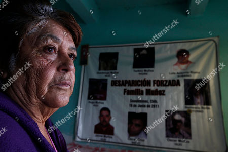 Emma Veleta, stands inside her home, backdropped by a poster that show her missing family members, on the outskirts of Cuauhtemoc, Mexico. Veleta holds out hope that the Argentine investigators can help find the eight disappeared members of her family