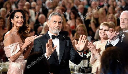 George Clooney, Amal Clooney, Nick Clooney. Actor/director George Clooney acknowledges applause from the audience as he arrives in the ballroom at the 46th AFI Life Achievement Award gala honoring him at the Dolby Theatre, in Los Angeles. Looking on are his wife Amal at far left and his father Nick at far right