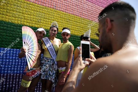Israelis and tourists pose for a photo as they participate American actress Gillian Iliana Waters in the gay pride parade in Tel Aviv, Israel, . The Tel Aviv Municipality said 250,000 people celebrated on Friday