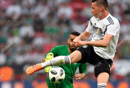 Germany's Julian Draxler, right, duels for the ball with Saudi Arabia's Mohammed Al-Breik during a friendly soccer match between Germany and Saudi Arabia at BayArena in Leverkusen, Germany