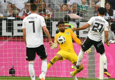 Saudi Arabia goalkeeper Abdullah Al-Mayouf, center, makes a save in front of Germany's Ilkay Gundogan, right, during a friendly soccer match between Germany and Saudi Arabia at BayArena in Leverkusen, Germany