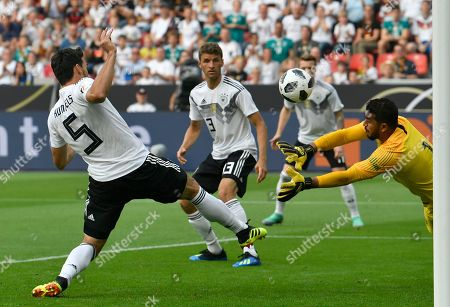 Stock Picture of Saudi Arabia goalkeeper Abdullah Al-Mayouf, right, makes a save in front of Germany's Mats Hummels, left, and Jonas Hector, center, during a friendly soccer match between Germany and Saudi Arabia at BayArena in Leverkusen, Germany