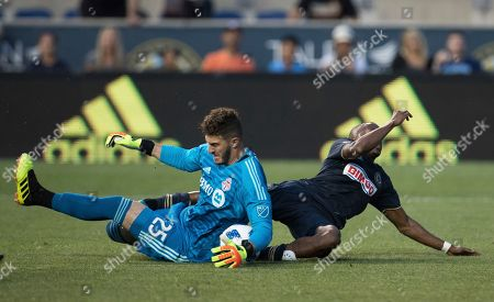Toronto FC's Alex Bono, left, makes the save on the shot by Philadelphia Union's Fafa Picault, right, during the first half of an MLS soccer match, in Chester, Pa