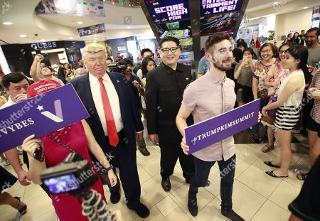 Kim Jong-un impersonator Howard X (R) and Donald Trump impersonator Dennis Alan (L) walk past shoppers as they make an appearance at the Bugis Junction shopping mall in Singapore, 09 June 2018. US President Donald J. Trump and North Korean leader Kim Jong-un are scheduled to meet at the Capella Hotel on Singapore's Sentosa Island for an historic summit on 12 June 2018.